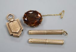 A Victorian yellow metal locket, two 9ct gold cased propelling toothpicks (one a.f.) and a brooch.
