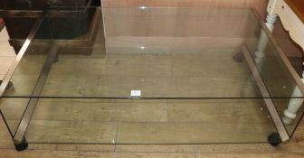 A modern chrome edged two tier plate glass coffee table, on castors W.136cm