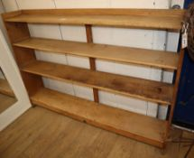 An Arts & Crafts pine three shelf open bookcase, with pegged joints W.168cm