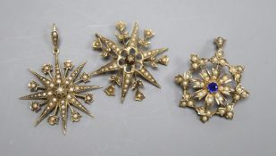 Three assorted Edwardian yellow metal and seed pearl set starburst pendants or brooches, including