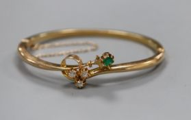 A diamond and emerald four stone set 15ct hinged bangle.