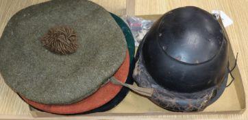 World War I leather helmet, a World War II tank regiment beret, two other berets, VAD badge, 1915