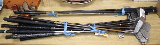 A collection of golf clubs, including five woods and approximately twenty irons (makers including
