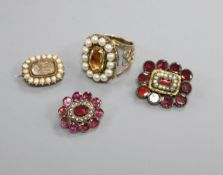 A 19th century yellow metal and seed pearl mourning brooch, two Victorian garnet brooches and an