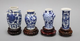 Four 19th century Chinese blue and white small vases, with hardwood stands tallest 9.5cm