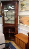A Georgian mahogany standing corner cupboard, blind fret-carved and astragal-glazed over open