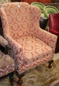 A 1920's upholstered tub framed armchair, with claw and ball feet