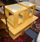 A beech two tier coffee table, with inset central glass panels and a pair of matching, smaller