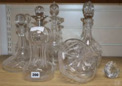 Eight glass decanters and claret jugs, some with silver wine labels