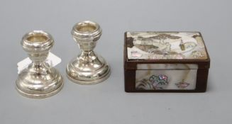 A mother of pearl snuff box and a pair of silver dwarf candlesticks