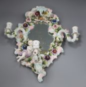 A floral encrusted porcelain three-branch wall mirror