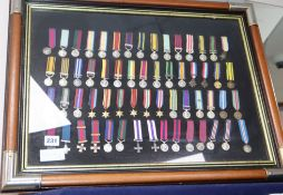 A framed collection of WWI and WWII miniature medals