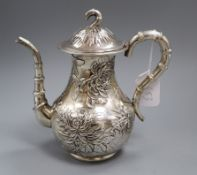 An early 20th century Chinese Export white metal coffee pot, embossed with chrysanthemums, maker