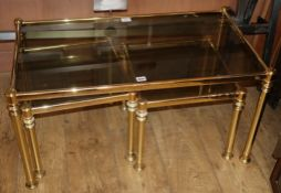 A nest of three modern gilt metal and smoked glass occasional tables W.90cm