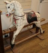 An early 20th century dapple grey wood rocking horse (lacking frame fixings) H.113cm