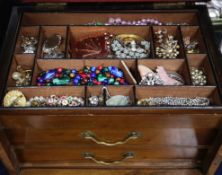 A Victorian brass inlaid walnut jeweller box, containing a quantity of costume jewellery.