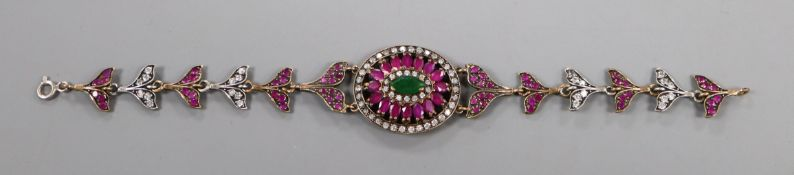 An Indian? yellow and white metal, ruby emerald and white sapphire set bracelet, 19cm.