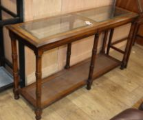 A reproduction walnut two tier side table, the top inset plate glass panels W.132cm