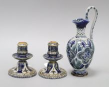 A Doulton Lambeth ewer, dated 1879, signed BE and RR? and a similar pair of squat candlesticks,