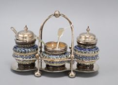 A Doulton Lambeth three piece cruet set, with plated mounts and frame, dated 1880, total width 19.