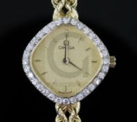 A lady's modern 14ct gold and diamond set Omega quartz dress wrist watch, the shaped dial with baton