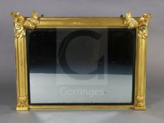 A William IV giltwood overmantel mirror, with foliate scroll capped pilasters, reeded ebonised