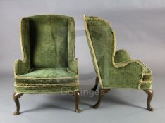 A pair of 19th century George I style mahogany wing armchairs, with scroll carved cabriole legs on