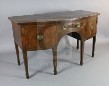 A George III mahogany bowfront sideboard, with central drawer flanked by a cupboard and deep drawer,