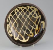 An English slipware circular baking dish, 18th / 19th century, decorated with a lattice design in
