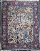 A North West Persian ivory ground rug, with various animals in a field of trees and foliage, with