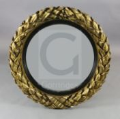 A fine large Regency giltwood and gesso convex wall mirror, with deeply carved ribbon tied laurel