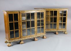 A pair of early 20th century feather banded walnut breakfront dwarf bookcases, with astragal