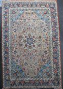 A Heriz ivory and blue ground carpet, with field of scrolling foliage and five row border, 13ft by