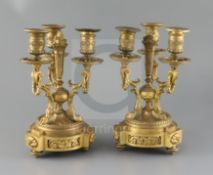 A pair of Louis XVI style ormolu candelabra, with central torch stems, triple foliate scrolled
