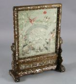 A Chinese embroidered silk, hongmu and mother of pearl framed table screen, c.1900, the