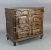 A late 17th century oak chest, of four long drawers with geometric moulded decoration, on stile