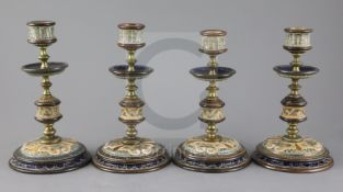 Frank A Butler for Doulton Lambeth, a set of four brass mounted candlesticks, c.1890, each incised
