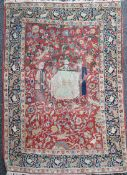 A Caucasian red ground rug, with three figures(one kneeling) in a field of scrolling foliage with