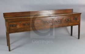 A George III oak dresser base, with planked top and four drawers, on squared tapered legs, W.7ft