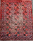 An Afghan aubergine and red ground carpet, with field of octagons and geometric motifs, 11ft 6in