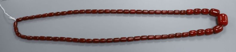 A single strand simulated cherry amber barrel shaped bead necklace, gross weight 84 grams, 96 cm.