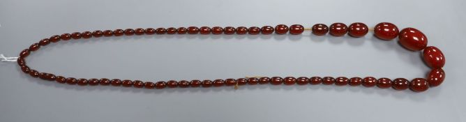 A single strand simulated cherry amber oval bead necklace, gross weight 93 grams, 100cm.