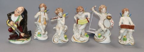 A Crown Naples figure of a hump back musician and five Capodimonte figures of cherubs