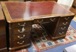 A George III style mahogany pedestal desk with gilt tooled burgundy leather top W.154cm