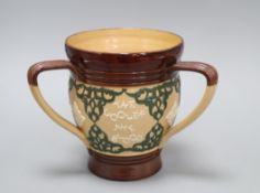 A Doulton Lambeth motto three-handled tyg, c.1895, inscribed 'THE SMALLER THE DRINK....', H. 17.3cm
