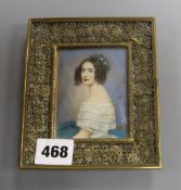An ivory-painted miniature of a lady in pierced brass frame