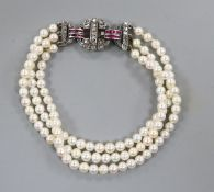 A triple strand cultured pearl bracelet with ruby and diamond set white metal clasp, 17cm.