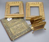 An Arts & Crafts brass blotter case, a pair of gilt frames and a letter rack