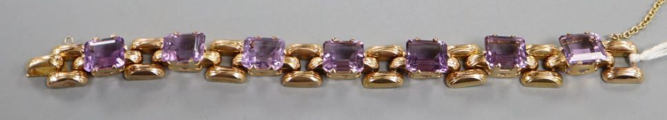 A yellow metal (tests as 18ct according to 1990 insurance valuation) and seven stone amethyst set