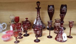 A collection of cranberry and engraved ruby glassware, including a decanter and stopper, a small